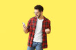 Leinwanddruck Bild - Happy young man with mobile phone on color background
