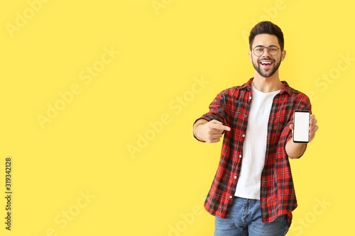 Obraz Happy young man with mobile phone on color background - fototapety do salonu