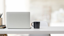 Close Up View Of  Workspace With Laptop, Office Supplies, Coffee Cup And Copy Space On White Desk