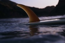 Surfboard Floating In The Ocean At Sunset