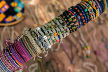 Close Up Of Row Of Colored Hand Made Bracelets In The Farmer's Market. Natural And Colored Strings, Beads, Small Stones. Blurry Background.
