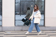 European model girl in a beige oversized down jacket, knitted sweater, jeans flared with a handbag and in glasses is walking along the street near glass windows. Life style