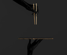 Abstract Sushi Bar Concept Background. Black Hands Using Gold Chopsticks And Sushi Dish Isolated On Black, 3d Illustration.