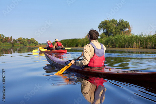 Valokuva Rear view of man paddling the wooden kayak and couple in red kayak kayaking in t