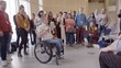 Audience listening to female inspirational speaker in wheelchair leading conference discussion