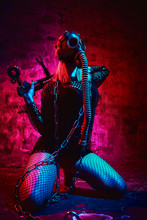 Female Model In Halloween Outfit In Gas Mask Posing With On A Red Background. Gorgeous Girl In Post-apocalypse Clothes Celebrates The Day Of The Dead. Halloween Concept, Witch Costume, Bright Colors