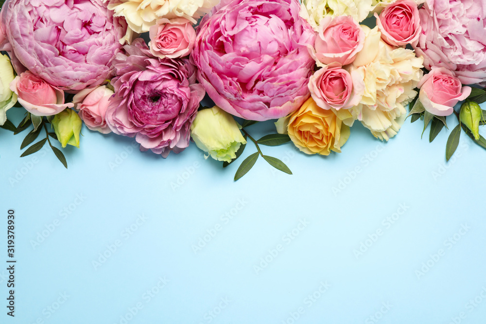 Fototapeta Flat lay composition with beautiful flowers and space for text on light blue background. Floral card design
