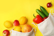 Leinwanddruck Bild - Cotton eco bags with fruits and vegetables on yellow background, flat lay. Space for text