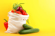 Leinwanddruck Bild - Cotton eco bag with vegetables on yellow background. Space for text