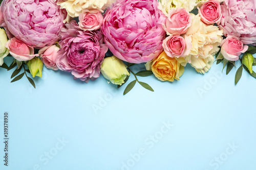 Obraz Flat lay composition with beautiful flowers and space for text on light blue background. Floral card design - fototapety do salonu