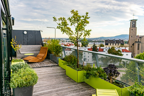 Fotografia Rocking lounger on a roof terrace with bamboo and grasses and outdoor furniture
