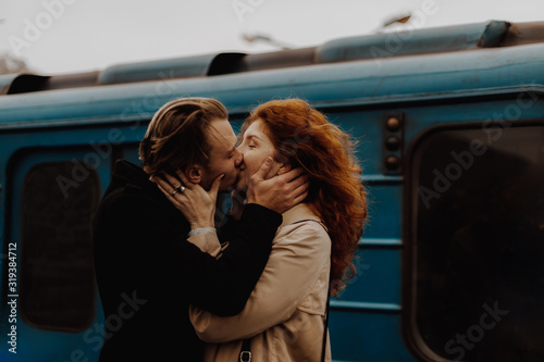 Young couple in love kissing against train in train station. Tableau sur Toile