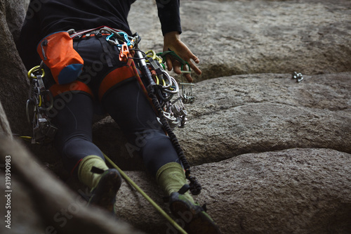 Climbing equipment on the harness of the climber on the background of a technical terrain, close-up.
