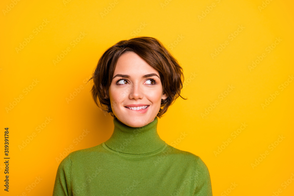 Fototapeta Closeup photo of funny pretty lady charming smiling good mood looking side empty space biting lips wear casual green warm turtleneck isolated yellow color background