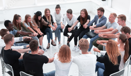 Obraz group of young like-minded people holding each other's hands - fototapety do salonu