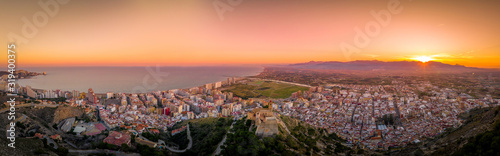 Fotografie, Tablou Aerial sunset view of Cullera church and castle with rectangular keep towering o
