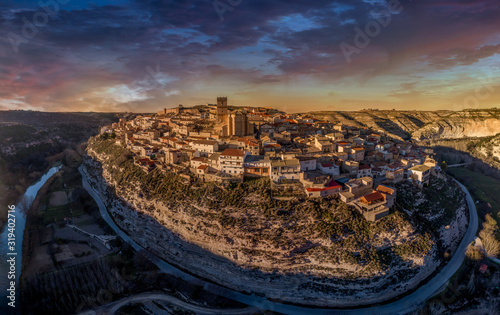 Aerial panoramic view of Jorquera town and castle above the Jucar river bend in Albacete province Spain with dramatic sunset sky
