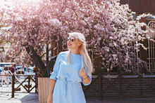 Beautiful Model In Blue Dress By Spring Blooming Tree