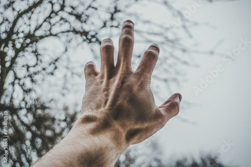 Photo male left hand reaching for dark blue sky with copy space for text