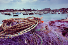 Normandy, France. Colorful Fishing Net Drying On Pier After Fishermen Back With Fresh Catch; Mooring Boats And Saint-Vaast-la-Hougue Houses At Background. Fishing Industry Concept. Retro Toned Photo.