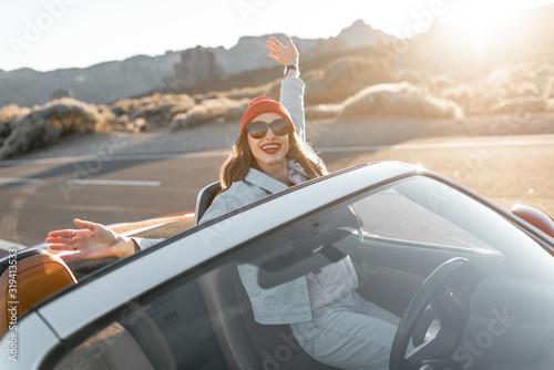 Lifestyle portret figlarnej kobiety, która bawi się podczas podróży, podnosząc ręce z kabrioletu podczas jazdy w pustynnej dolinie na zachodzie słońca
