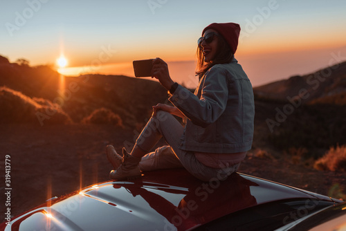 Young woman photographing with phone beautiful landscape during a sunset, sitting on the car hood while traveling high in the mountains - 319413779