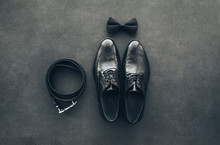 Stylish Black Lacquered Men's Shoes, Leather Belt And Bow Tie On Vintage Dark Grey Background. Men's Accessories. Groom Set. Top View, Copy Space.