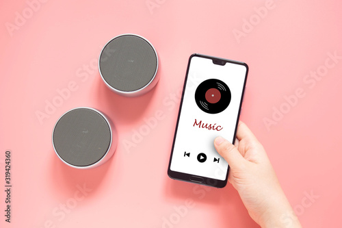 Top view of woman hands holding smartphone with music media player application and connect wireless bluetooth speaker portable on coral color background Canvas Print