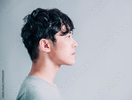 Cuadros en Lienzo side view of young smiling handsome man isolated on gray background