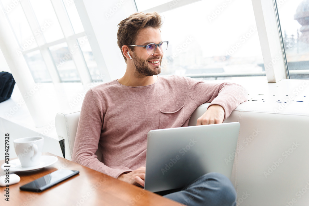 Fototapeta Image of man wearing earbuds working on laptop computer in cafe indoors