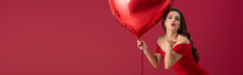 Panoramic Shot Of Seductive, Elegant Girl Holding Heart-shaped Balloon And Sending Air Kiss At Camera Isolated On Red