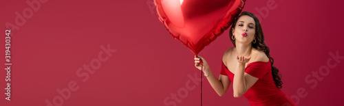 Платно panoramic shot of seductive, elegant girl holding heart-shaped balloon and sendi