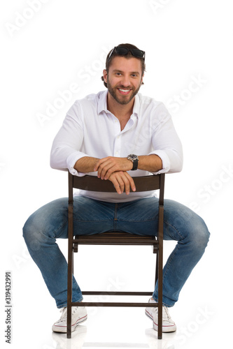 Photo Handsome Smiling Man Is Sitting Astride A Chair. Front View.