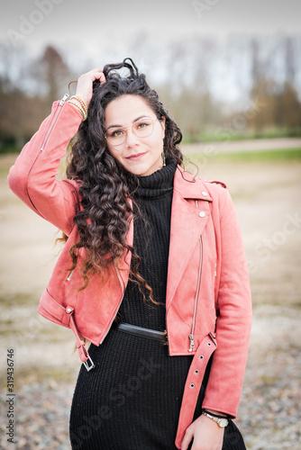 Fotografía belle jeune femme brune au cheveux longs avec lunette et veste en cuir rose