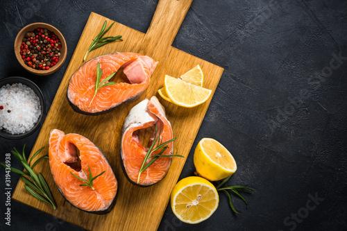Fotografie, Obraz Raw salmon steak on black top view.