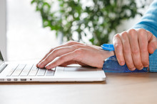 Close Up Of Man Applying Cold Compress To A His Painful Wrist Caused By Prolonged Work On The Computer, Laptop. Carpal Tunnel Syndrome, Arthritis, Neurological Disease Concept.