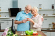 Leinwanddruck Bild - Selective focus of smiling senior couple toasting with champagne by vegetables and flowers on kitchen table