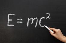 A Hand Writing 'E=mc2' On Chal...