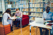 Diverse students doing homework near bookshelves