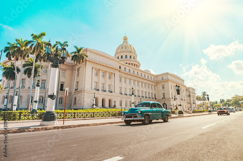 Photo vintage American retro car rides on an asphalt road in front of the Capitol in old Havana