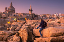 Man Sitting On The Rock And Watch Beautiful Architecture Of The Valletta City At Dawn, Malta