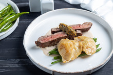 Grilled Meat Steak New York Striploin. Dumplings With Porcini Mushrooms In Asparagus Truffle Sauce. On A Wooden Board On A Dark Background.