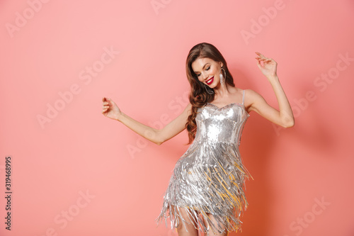 Obraz Smiling young woman in bright sequins dress - fototapety do salonu