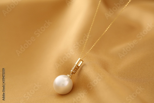 Photo Platinum pearl pendant inlaid with diamonds and gold