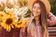 Happy Woman Admiring Flowers O...