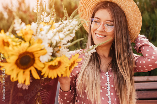 Happy woman admiring flowers on summer day Canvas Print