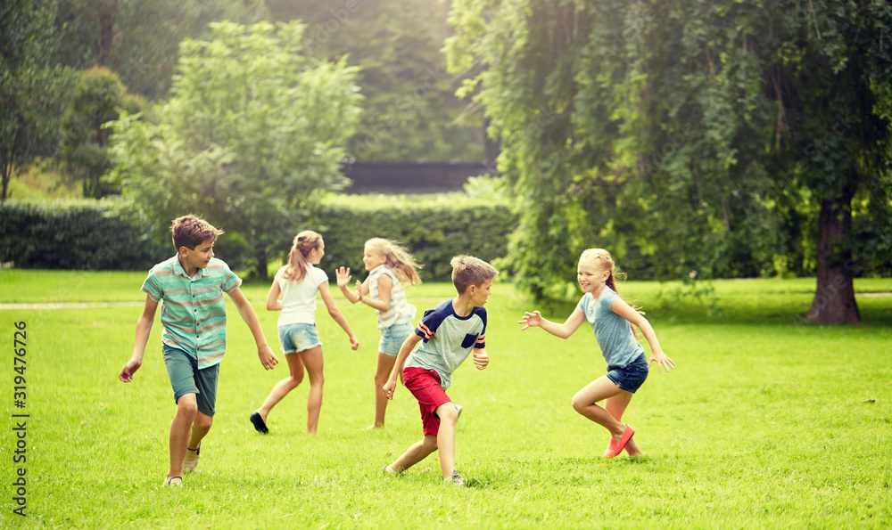 Fototapeta friendship, childhood, leisure and people concept - group of happy kids or friends playing catch-up game and running in summer park