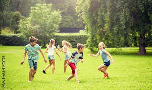 Obraz friendship, childhood, leisure and people concept - group of happy kids or friends playing catch-up game and running in summer park - fototapety do salonu