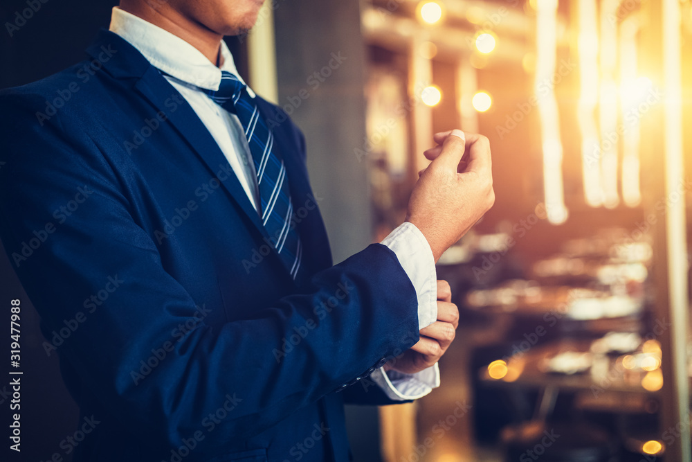 Fototapeta businessman wearing business suit fasten cufflink or button on sleeve of classic jacket and factory background.