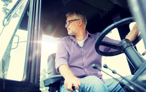 farming, agriculture and people concept - senior man driving tractor at farm Tableau sur Toile